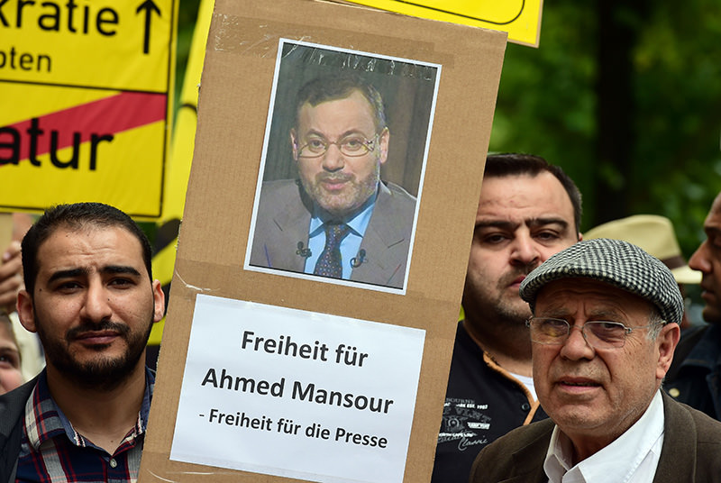Supporters of Mohamed Morsi stage a demonstration to ask for the release of detained Al-Jazeera journalist Ahmed Mansour in front of the local court of Berlin's Tiergarten district, on June 21, 2015 (AFP Photo)