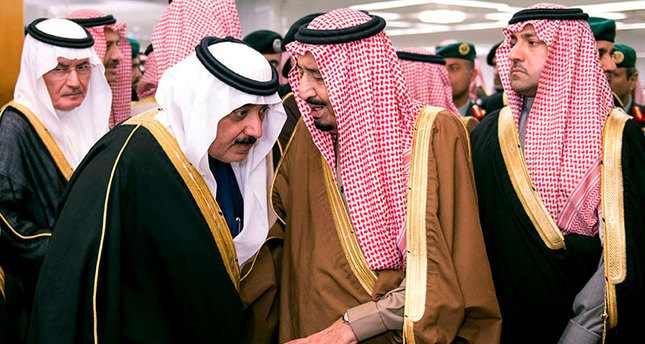Saudi King Salman, center, speaks to Crown Prince Muqrin, center left, in the king's dewaniya, a traditional Arab reception area to receive guests, where condolences for Saudi King Abdullah, are being received, in Riyadh, Saudi Arabia. (AP Photo)