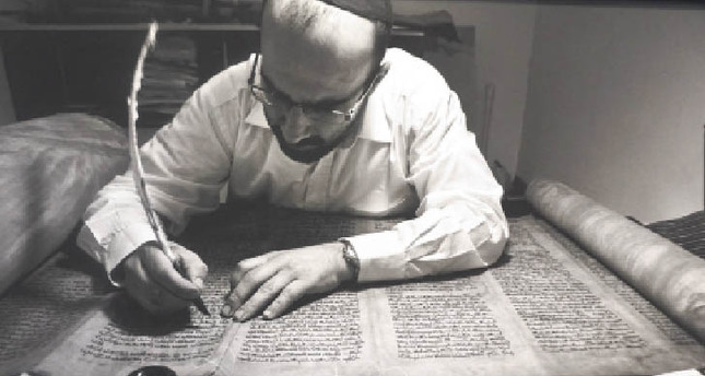 A Jewish-Turkish resident working on a Sefer Torah, which is a handwritten copy of the Torah