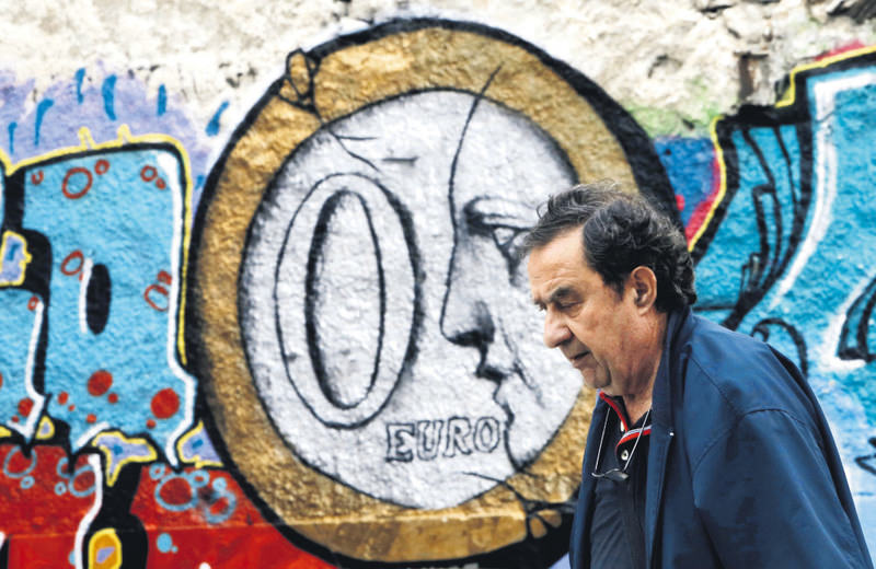 A man walks in front of a wall covered with graffiti depicting a zero euro coin in central Athens yesterday.