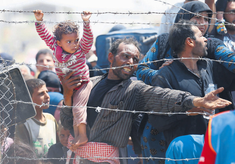 A Syrian refugee holds on to his daughter as he waits to cross into Turkey at Aku00e7akale border gate in u015eanlu0131urfa province on June 15.