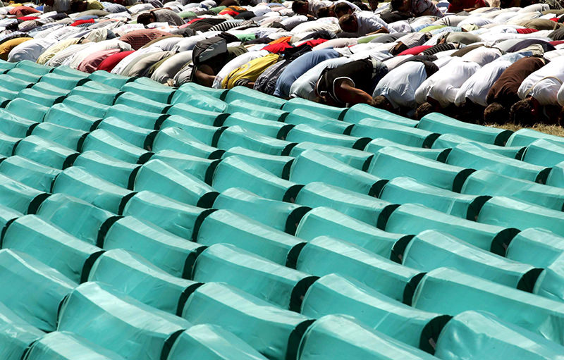 Bosnian Muslims praying near coffins at the Potocari Memorial Center during the burial of 308 Bosnian Muslims killed by Bosnian Serb forces in Srebrenica. July 2015 marks the 20-year anniversary of the Srebrenica Massacre (EPA Photo)