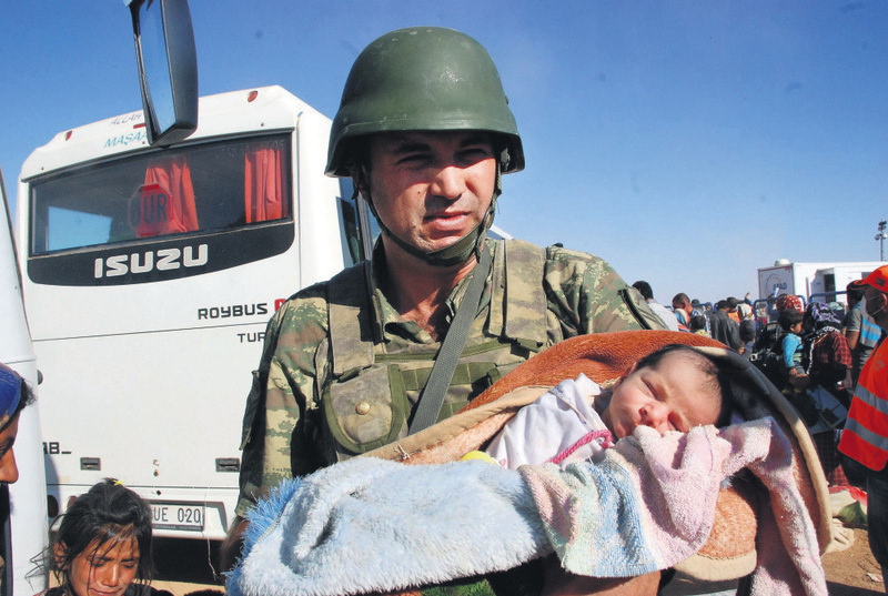 Ferman, cradled by a Turkish soldier on the border, was born in a Turkish border town her mother took shelter in minutes after the Syrian family which fled Kobani in Syria, arrived there last year.