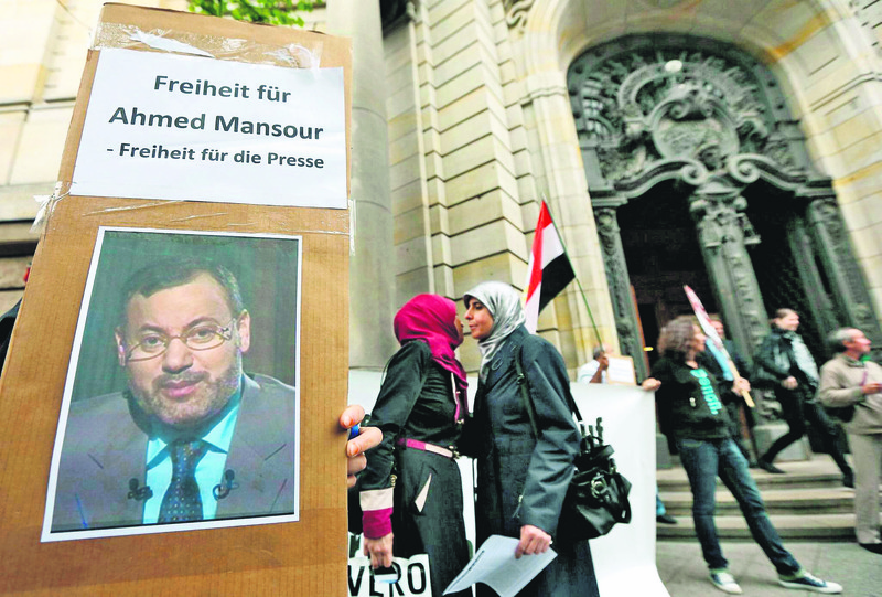 People outside the court hold signs saying, u2018freedom for Mansour, freedom of press'.