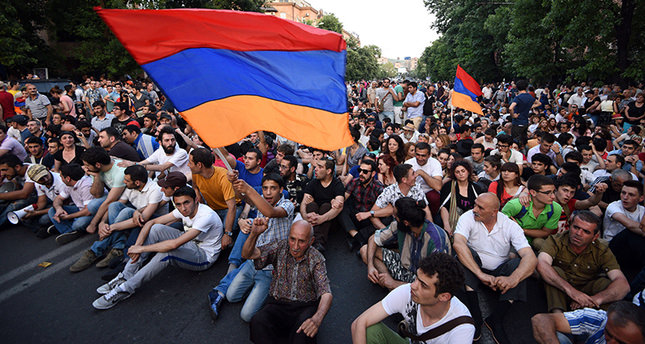 Demonstrators wave their national flags as they sit during a protest against the increase of electricity prices in Yerevan, the capital of Armenia, on June 22, 2015. (AFP Photo)