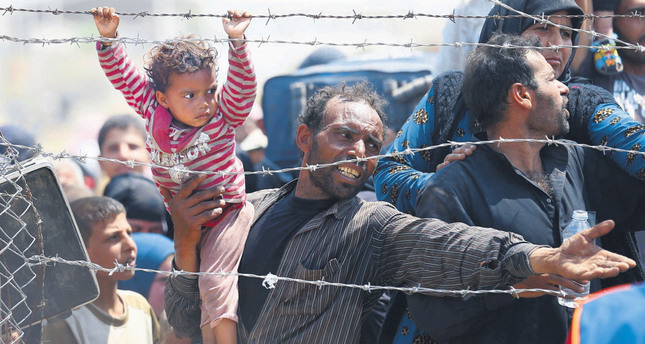 A Syrian refugee holds on to his daughter as he waits to cross into Turkey at Akçakale border gate in Şanlıurfa province on June 15. (Reuters Photo)