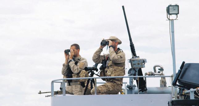 Belgian navy members watch the Mediterranean Sea to inspect human smugglers.
