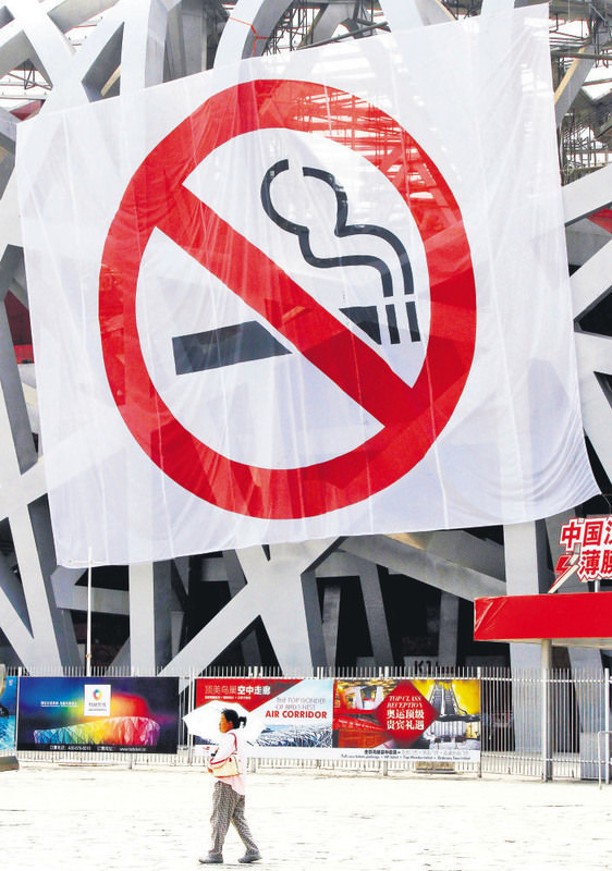A large anti-smoking banner hangs on the exterior of the Bird's Nest stadium as a tourist walks by in Beijing, China. Beijing implemented a new smoking ban that took affect June 1.