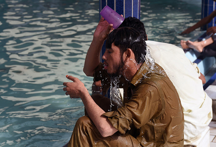 A Pakistani man cools down with water at a mosque during a heatwave in Karachi on June 22, 2015 (AFP Photo)