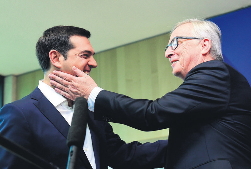 Greek Prime Minister Alexis Tsipras (L) is welcomed with a friendly pat by European Commission President Jean-Claude Juncker ahead of an emergency leaders' summit on Greece at the European Commission in Brussels on Monday.