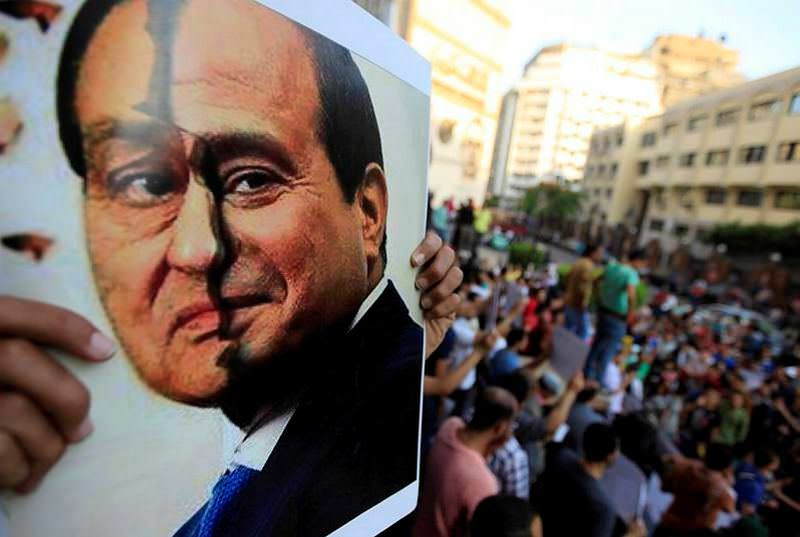 A poster shows a placard with the faces of Egypt's ousted President Hosni Mubarak (L) and the current President Abdel-Fattah el-Sissi as Sissi has been following an oppressive policy similar to Mubarak's, toward the Muslim Brotherhood.