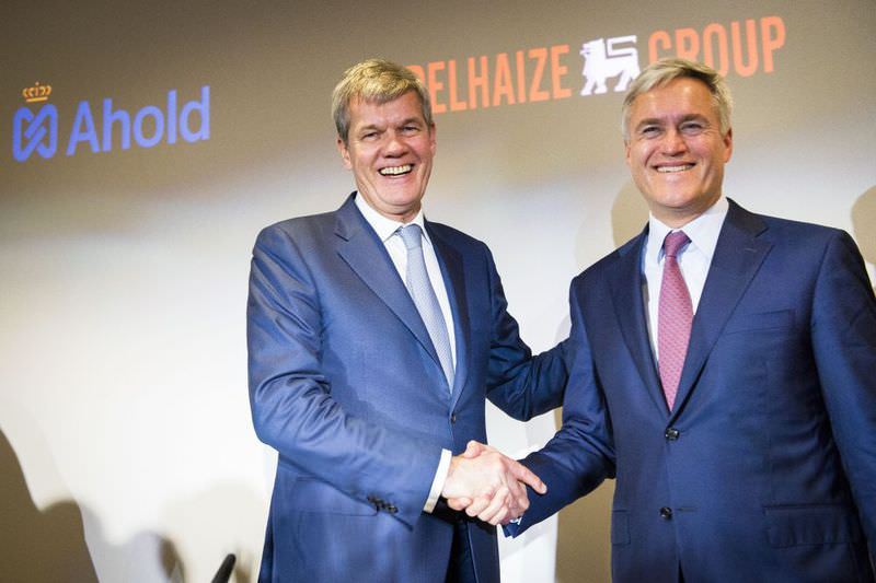 CEO of Dutch retail giant Ahold Dick Boer (L) shakes hands with his counterpart at Belgian rival Delhaize Frans Muller prior to a press conference yesterday in Brussels.