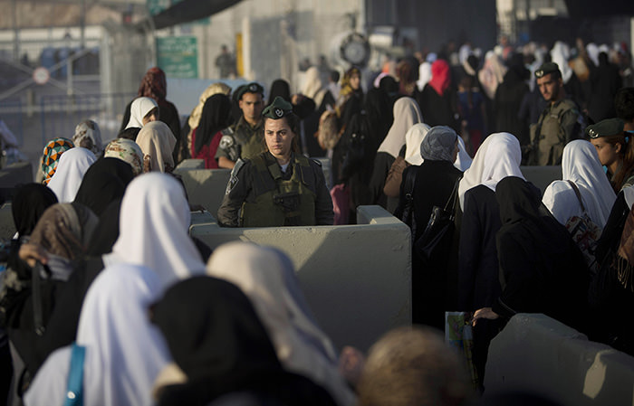 Palestinian women walk past an Israeli border police officer on their way to pray at the Al-Aqsa Mosque in Jerusalem (AP Photo)
