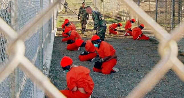 Detainees kneel in a cage in Guantanamo Bay detainment camp