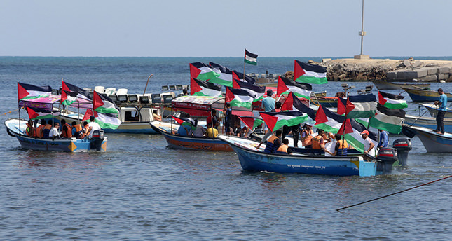 Palestinians hold their national flag to show support for activists aboard a flotilla of boats who are soon to set sail for Gaza at the seaport of Gaza City on June 24, 2015 (AFP Photo)