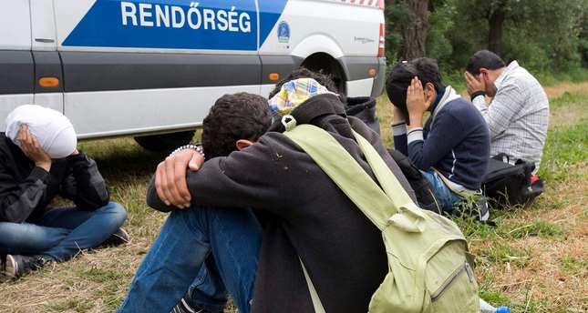 Migrants who were captured on a small island in the Tisza River next to a police van near Serbian border.