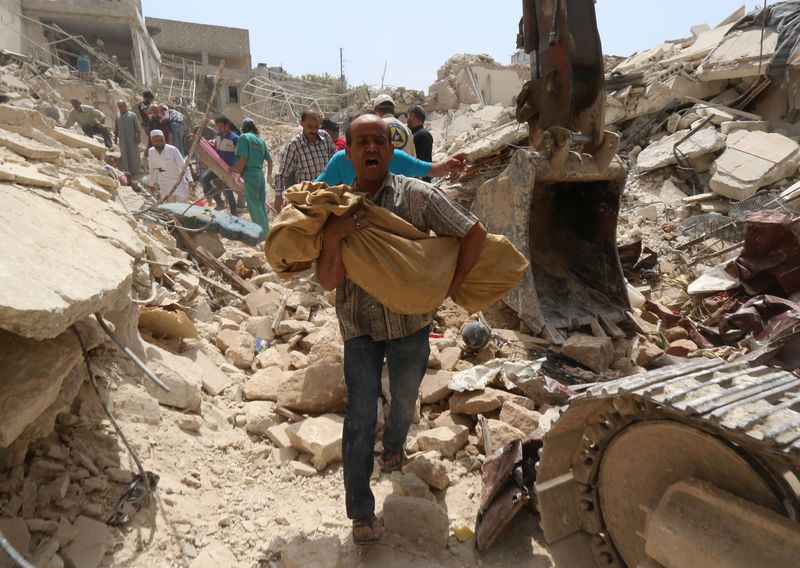 A Syrian man carries a body after it was removed from the rubble of buildings following a reported barrel bomb attack by government forces on the Qadi Askar district of the northern Syrian city of Aleppo on May 20, 2015. (AFP Photo)