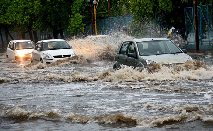Indian commuters make their way through a water logged street during heavy rain in Bhopal, India, 22 June 2015 (EPA Photo)