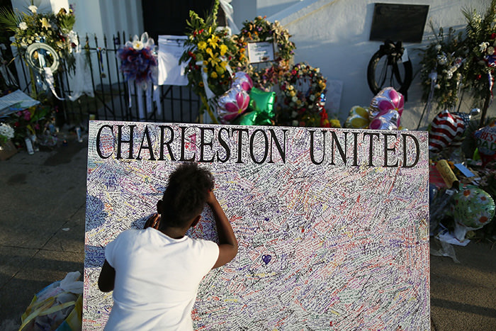 Jennice Barr, 10, leaves a message on a board set up in front of the Emanuel African Methodist Episcopal Church after a mass shooting at the church killed nine people, on June 22, 2015 (AFP Photo)
