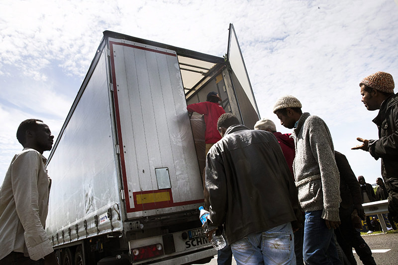 Migrants climb in a truck in order to reach Britain through the Channel Tunnel in Calais, France. The blockade of the port provoked a huge traffic jam of trucks, a golden opportunity for migrants to jump in and try to reach Britain. (EPA Photo)
