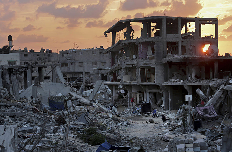 Palestinians walk during the sunset between the rubble of their destroyed building in Shijaiyah neighborhood of Gaza City in the Northern Gaza Strip, Oct. 12, 2014 (AP Photo)