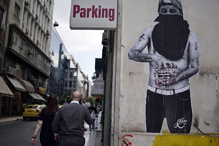 People walk past a mural depicting a person holding a bleeding Euro sign in central Athens on June 25, 2015 (AFP Photo)