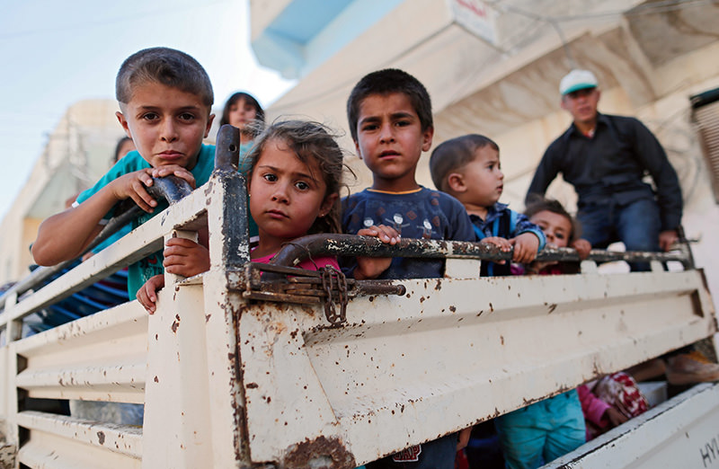 Syrian children are carried by a truck in east of Kobane in Syria, 22 June 2015 (EPA Photo)