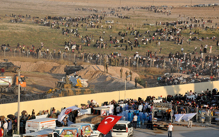 Syrian refugees from Tel Abyad (foreground) line up at the border crossing as the others wait behind the fences to cross into Turkey at the Akcakale border gate in Sanliurfa province, Turkey, June 14, 2015 (Reuters Photo)