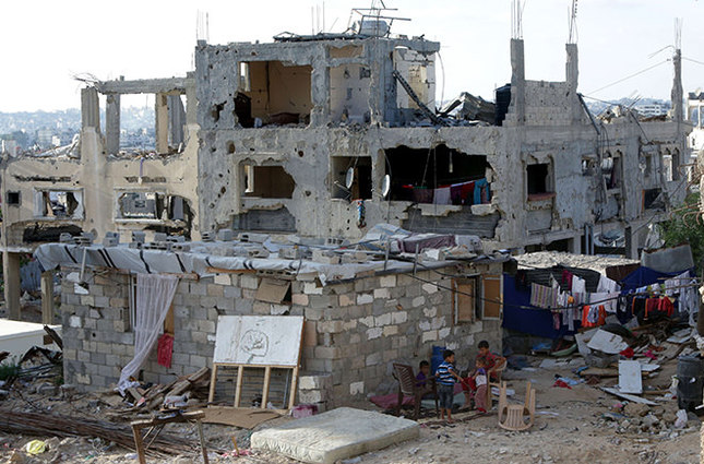 Palestinian children play next the remains of their house on June 22, 2015 in Gaza City that was destroyed during 50-day war between Israel and Hamas-militants in the summer of 2014. (AFP Photo)