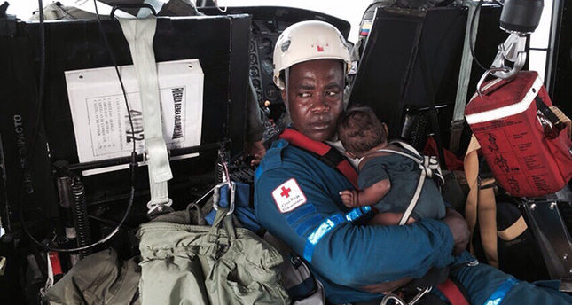 Handout photo released on June 24, 2015 of a Red Cross member holding baby Yudier Moreno as he and his mother are transported on a helicopter to a hospital in Colombia (AFP Photo)