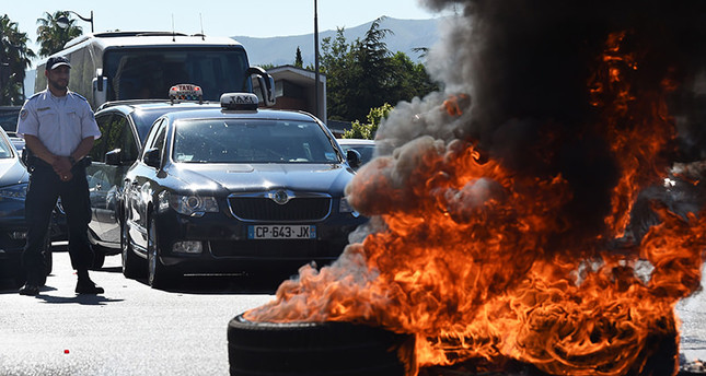 French Taxi drivers burn tires as they protest in the southern city of Marseille on June 25, 2015 as they demonstrate against UberPOP, a popular taxi app that is facing fierce opposition from traditional cabs. (AFP Photo)
