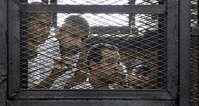 A group of journalists appear in a cage in a court room in Cairo, Egypt (AP Photo)