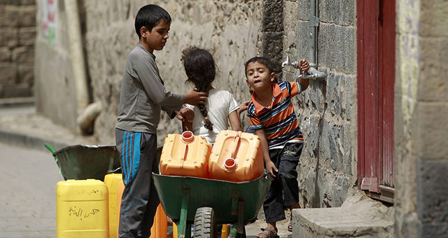 Yemeni children carry jerrycans to fill them with water from a public tap amid an acute shortage of water supply to houses during the fasting month of Ramadan in the capital Sanaa, on June 21, 2015 (AFP PHOTO)