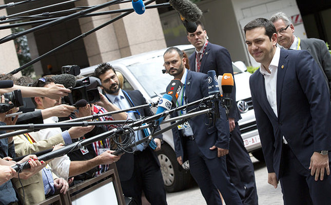 Greek Prime Minister Alexis Tsipras speaks with the media as he arrives for an EU summit in Brussels on Thursday, June 25, 2015 (AP Photo)