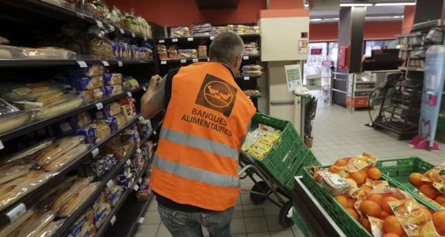 Guy, a retired train engineer, who volunteers at the Banques Alimentaires (Food Bank), pushes a trolley with food goods donated by a supermarket to charity organisations in l'Hay-les-Roses, France.