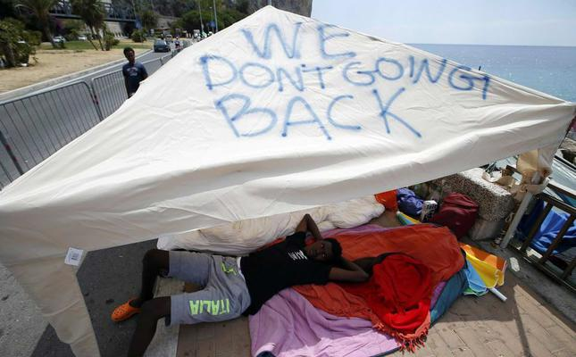 A migrant lies in the shade of a tent with the words We don't going back written on it in the Italian city of Ventimiglia on the Italian-French border (AFP Photo)