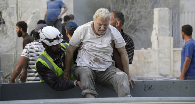 Residents help an injured man at a site attacked by barrel bomb by Syria's regime forces in Maarat Al-Nouman, south of Idlib June 8, 2015. (Reuters Photo)