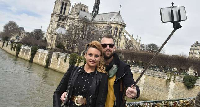 photo shows tourists as they use a selfie-stick to take a picture of themselves near the Notre Dame cathedral in Paris. (AFP Photo)