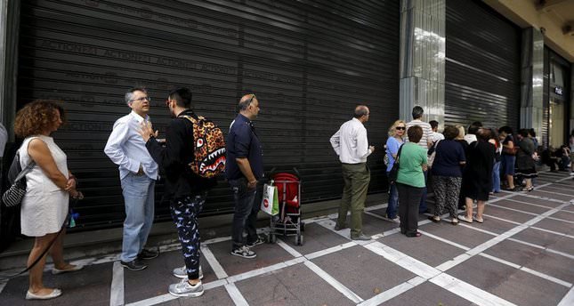 People wait outside a closed branch of Piraeus Bank in Athens, Greece June 27, 2015 (Reuters Photo)