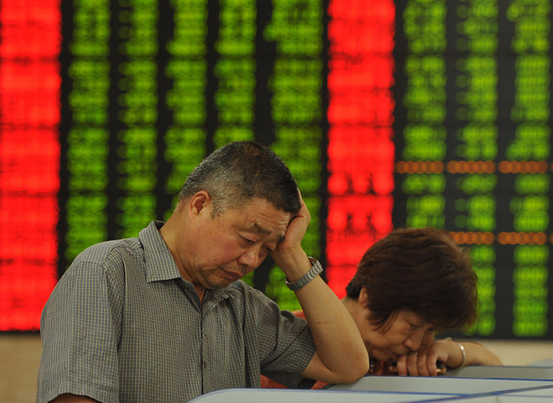 This photo taken on June 26, 2015 shows investors checking the share prices in a stock firm in Fuyang, east China's Anhui province (AFP Photo)