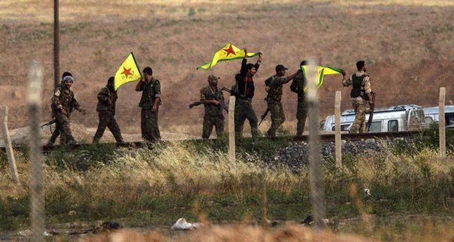 Kurdish  YPG fighters hold their movement's flag near the Akçakale crossing gate between Turkey and Syria at Akçakale in Şanlıurfa province (AFP Photo)