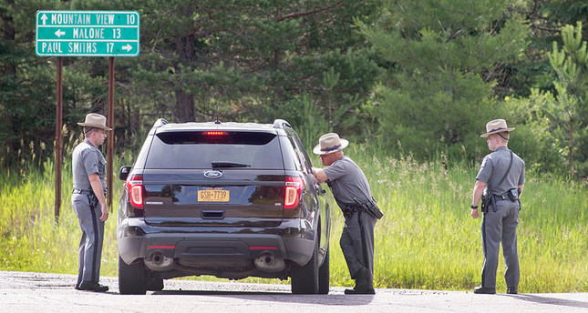 New York State Police officers man a roadblock along Highway 30 as the manhunt for escaped convict David Sweat continues on June 27, 2015 near Malone, New York. (AFP Photo)