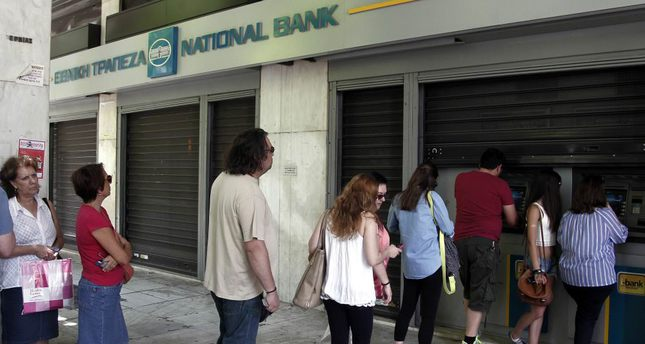 People wait in a queue to withdraw money from an ATM outside a branch of Greece's National Bank in Athens yesterday. Greek PM Tsipras called for a referendum on the Greek debt deal on July 5.