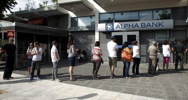 People wait in a queue to withdraw money from an ATM outside a branch of Greece's Alpha Bank in Athens, Greece, 27 June 2015. (EPA Photo)