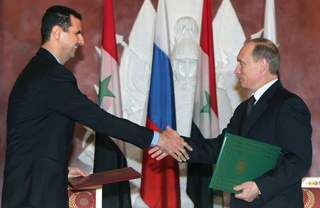 Putin and Assad shake hands in Kremlin during Assad's visit to Moscow in 2005 (AP Photo)
