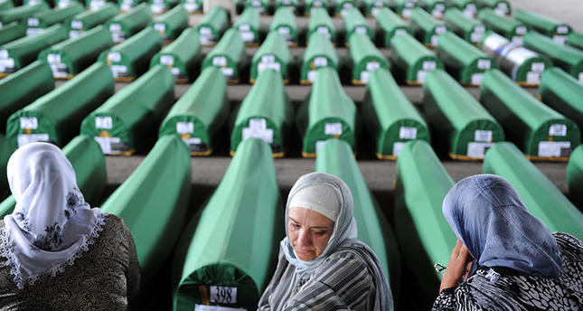 Bosnian Muslim women cry and pray among 520 caskets stocked in an abandoned factory hangar, in preparation for a mass burial ceremony at the Srebrenica Memorial Cemetery, in Potocari on July 10, 2012 (AFP Photo)