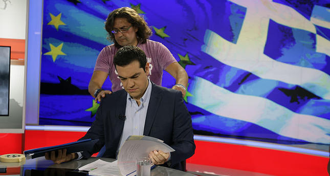 Greece's Prime Minister Alexis Tsipras takes a look at his notes as a technician prepares him before a TV interview at the State Television (ERT) in Athens, Monday, June 29, 2015 (AFP Photo)