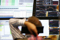 A trader sits in front of the computer screens at his desk at the Frankfurt stock exchange, Germany (Reuters Photo)