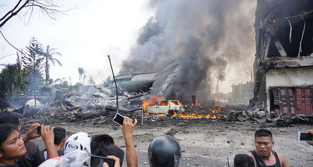 People look at a military plan crash in Medan on June 30, 2015. An Indonesian military transport plane crashed on June 30 shortly after taking off and exploded in a ball of flames in a residential area. (AFP Photo)