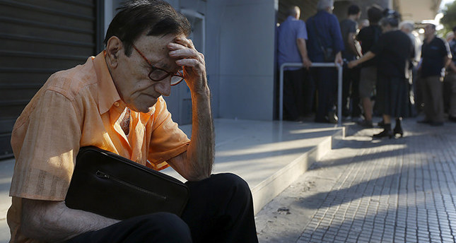Giorgos, a 77-year-old pensioner from Athens, sits outside a branch of the National Bank of Greece as he waits along with dozens of other pensioners, hoping to get their pensions in Athens, Greece June 29, 2015 (Reuters Photo)